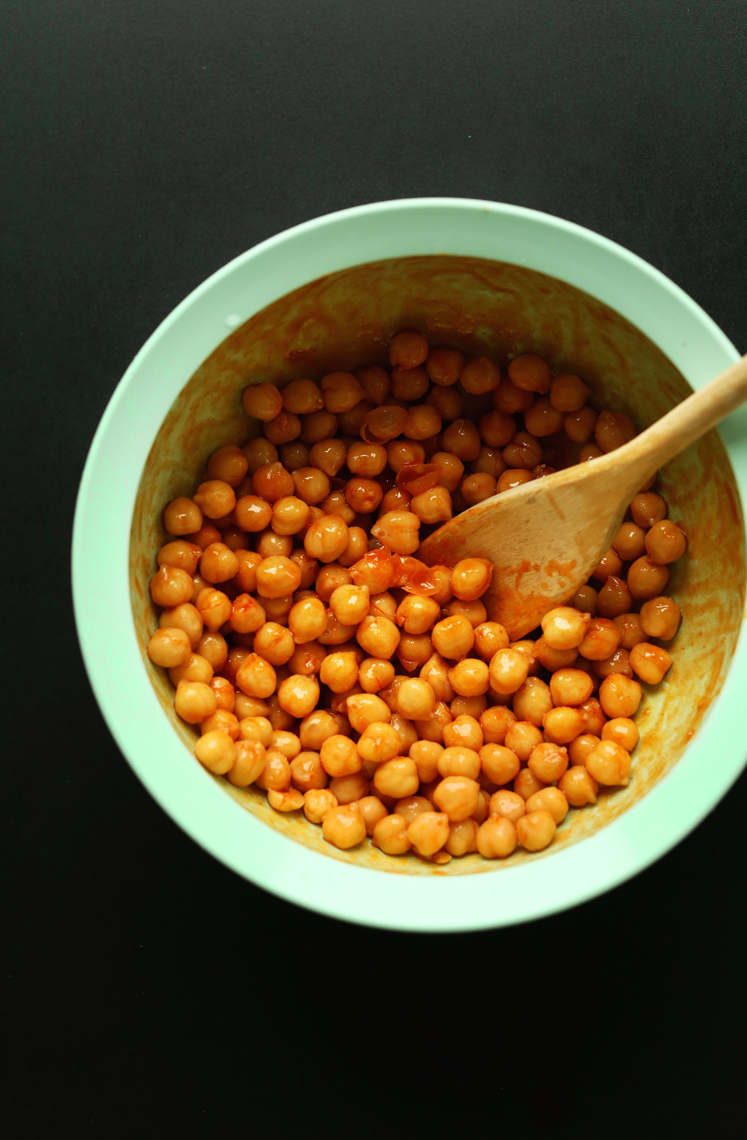 Stirring buffalo-style sauce onto chickpeas for a protein-packed vegan meal