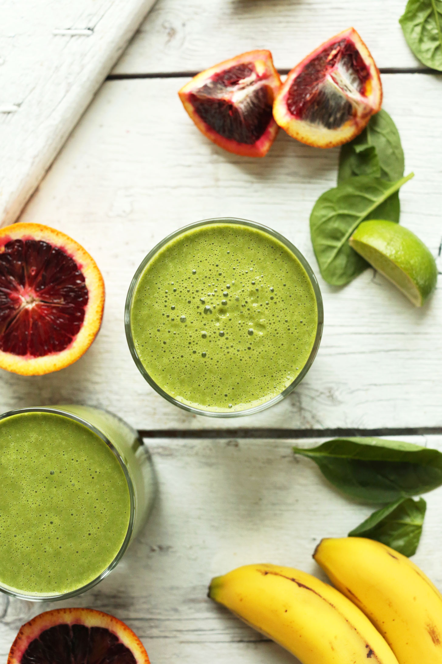 Glasses of our vegan Blood Orange Green Smoothie surrounded by key ingredients such as banana, blood orange, and spinach