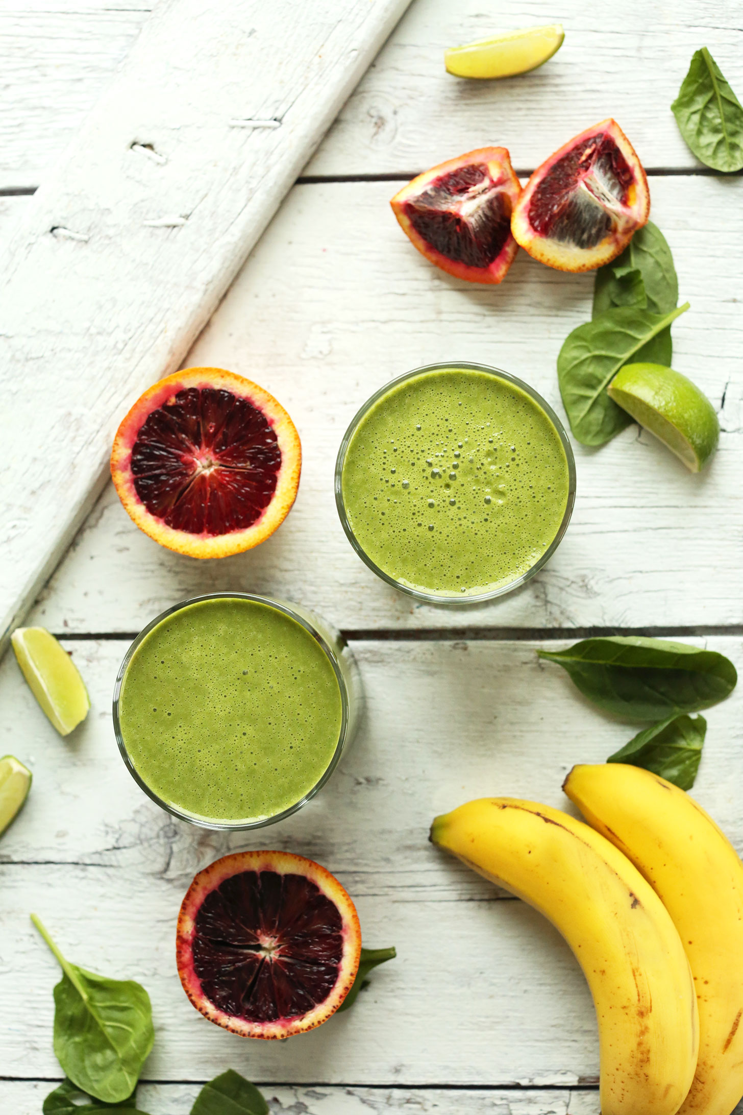 Two glasses of vegan Blood Orange Green Smoothie made with blood oranges, lime, spinach, and bananas