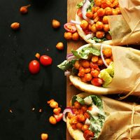 Cutting board with three Spicy Chickpea Wraps tied with parchment paper and twine
