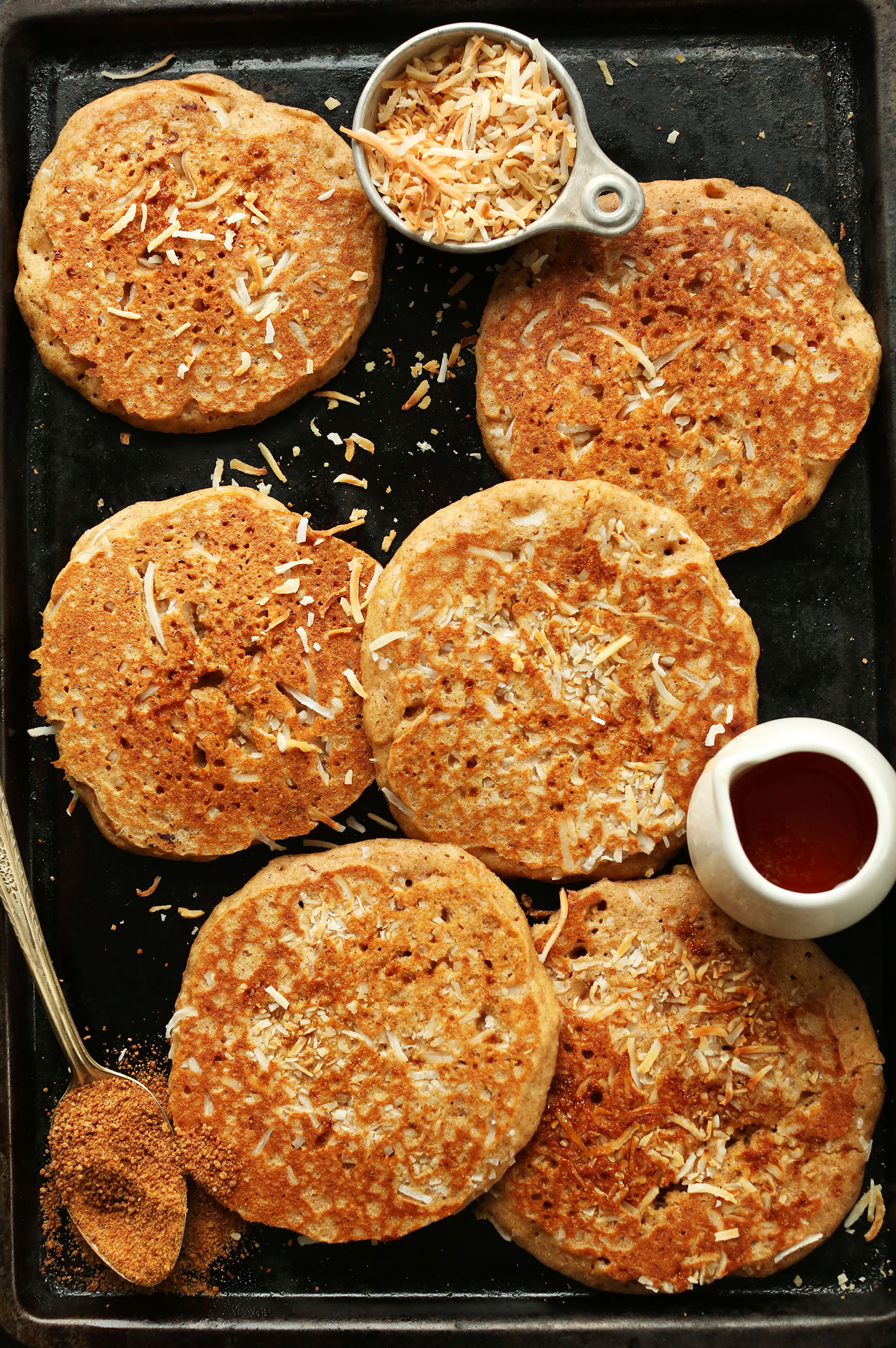 Baking sheet with freshly made vegan Toasted Coconut Pancakes and maple syrup for serving