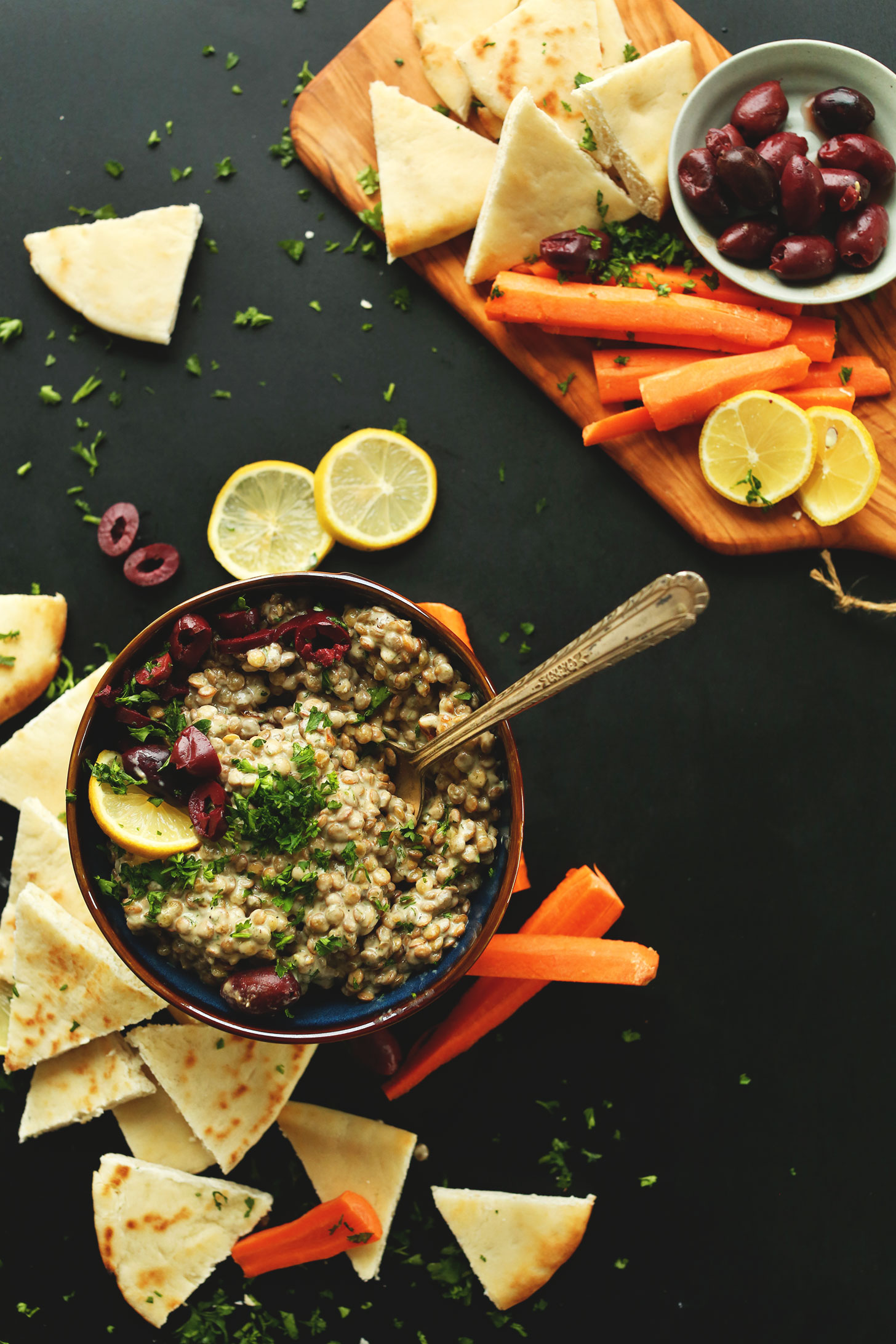 Bowl of our delicious Mediterranean Lentil Dip recipe alongside pita bread and carrot sticks for dipping