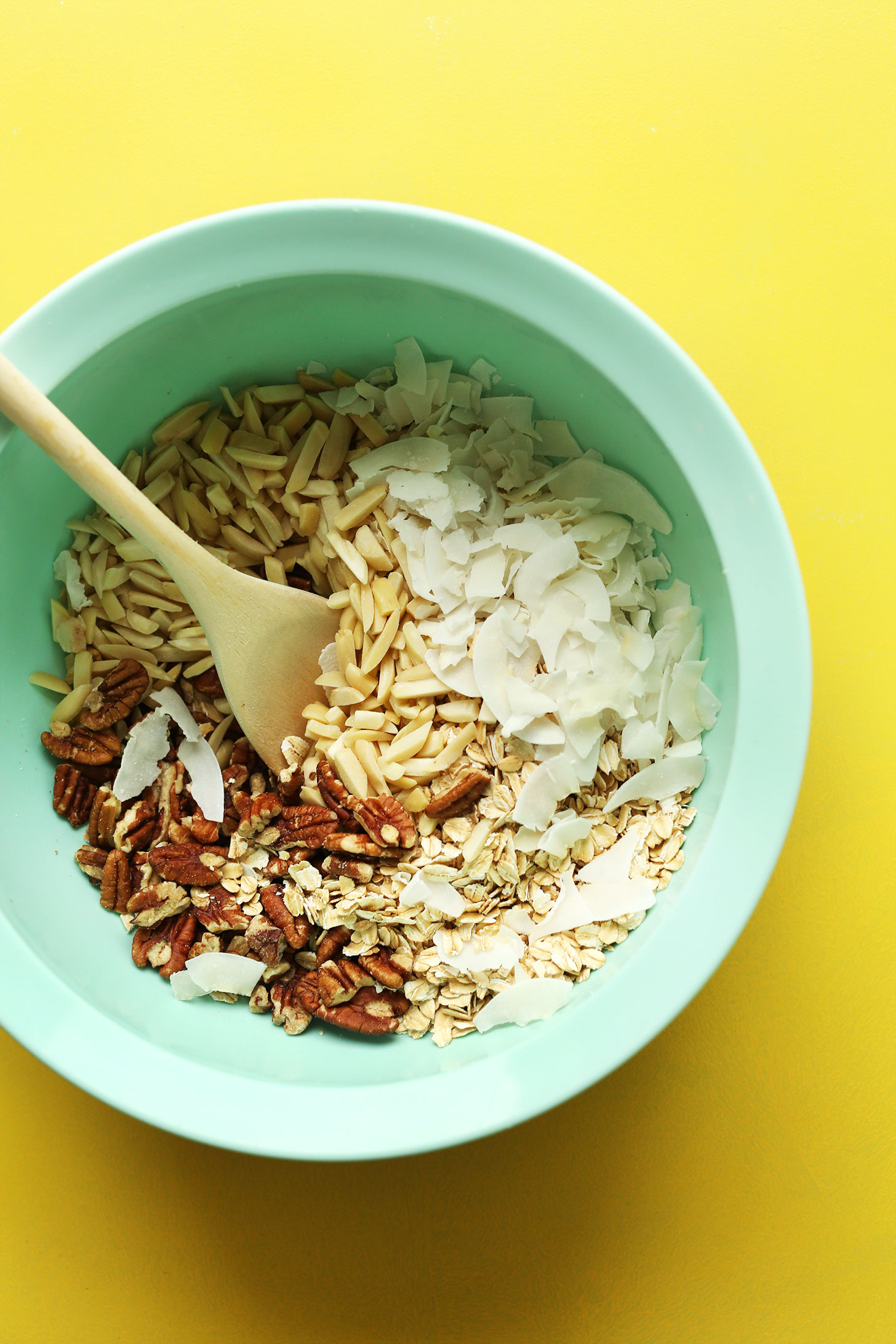 Mixing bowl with oats, nuts, and coconut for making gluten-free naturally-sweetened granola