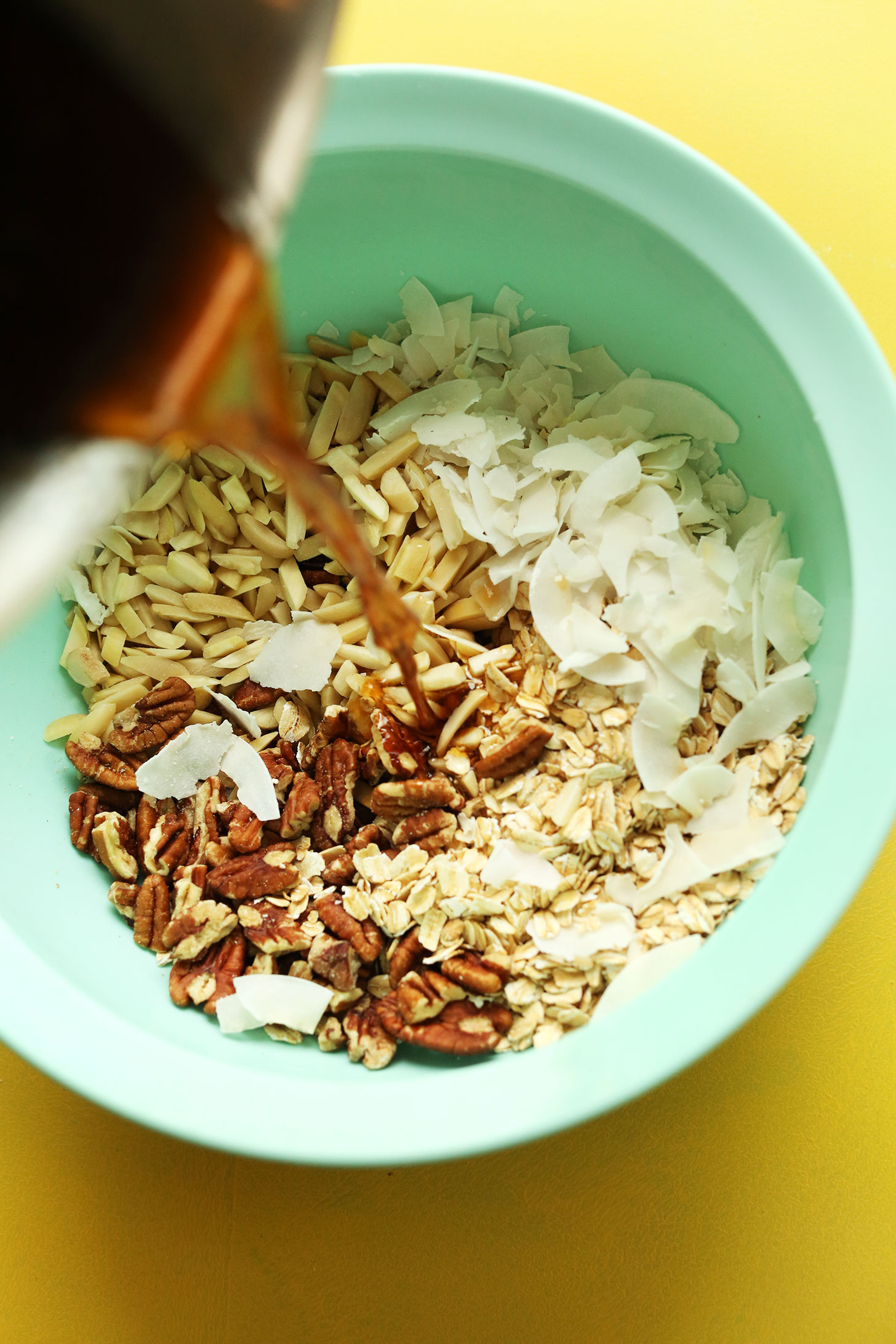 Pouring melted coconut oil maple syrup mixture into dry ingredients for homemade vegan coconut granola