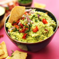 Dipping a cracker into our delicious plant-based Greek-Inspired Guacamole recipe