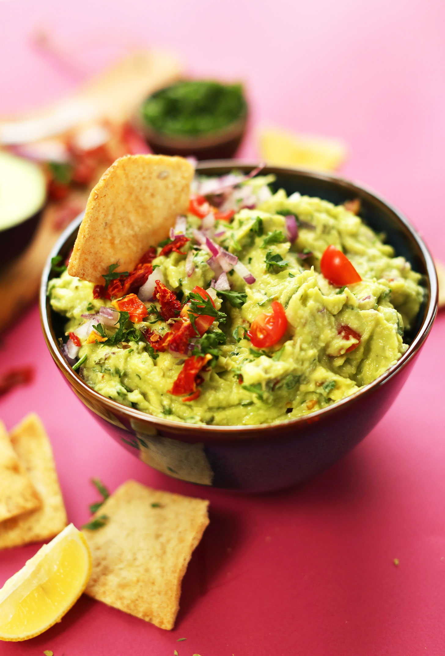 Bowl of our delicious Greek-inspired Guacamole made with sun-dried tomatoes, red onion, lemon juice, and oregano