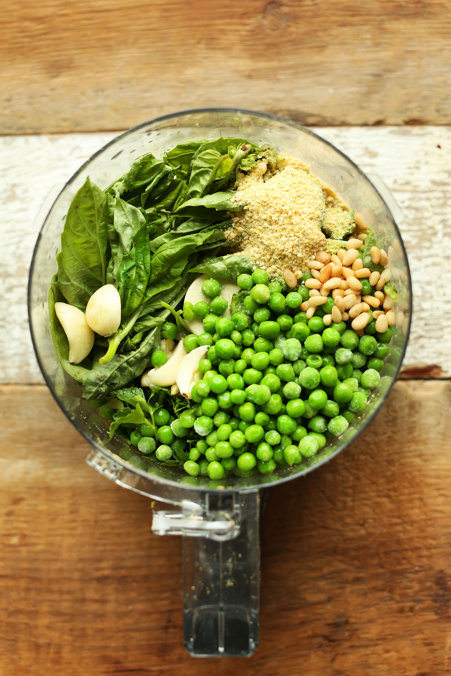 Food processor with ingredients for making our homemade vegan Pea Pesto recipe