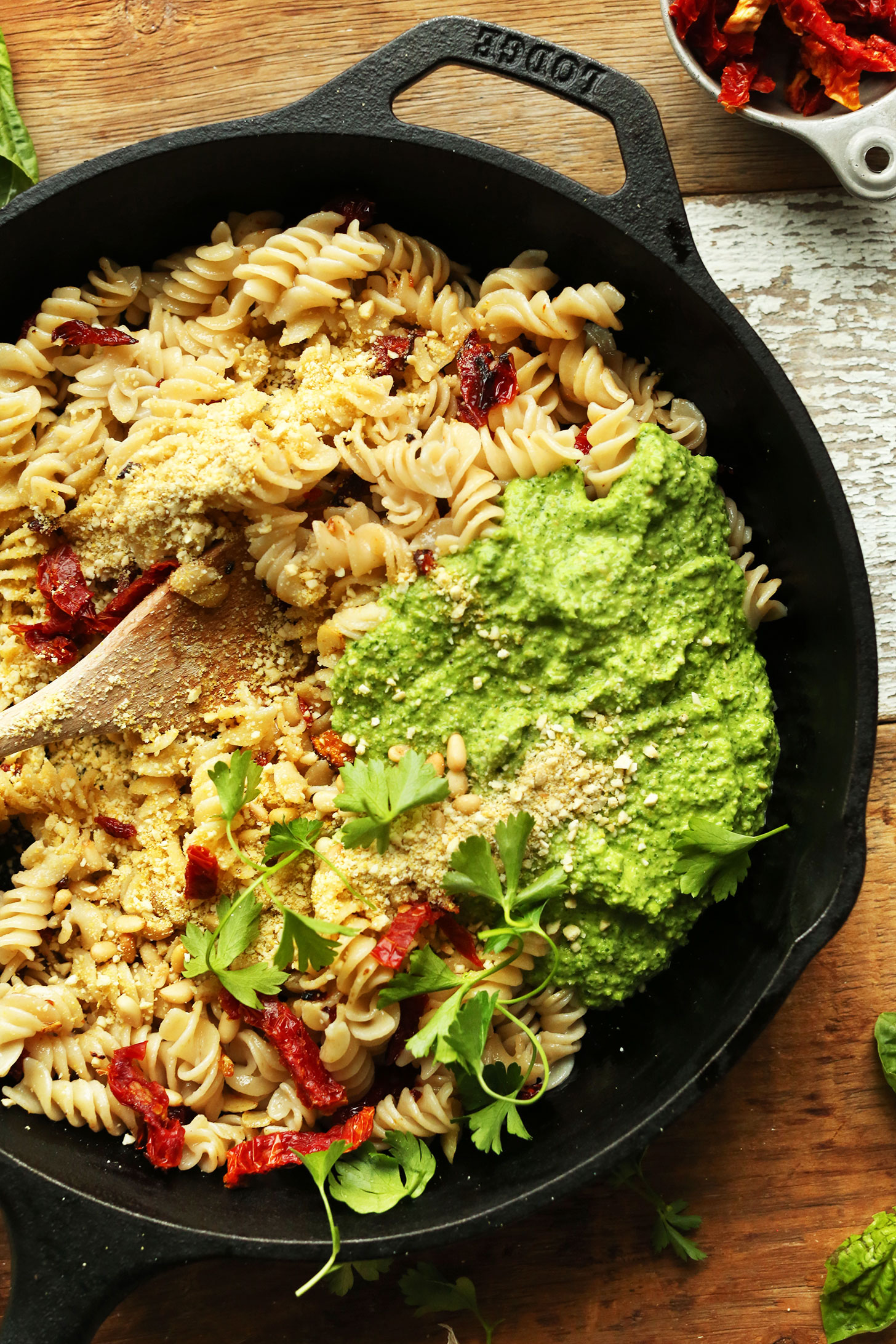Cast-iron skillet with gluten-free noodles, sun-dried tomatoes, and pea pesto