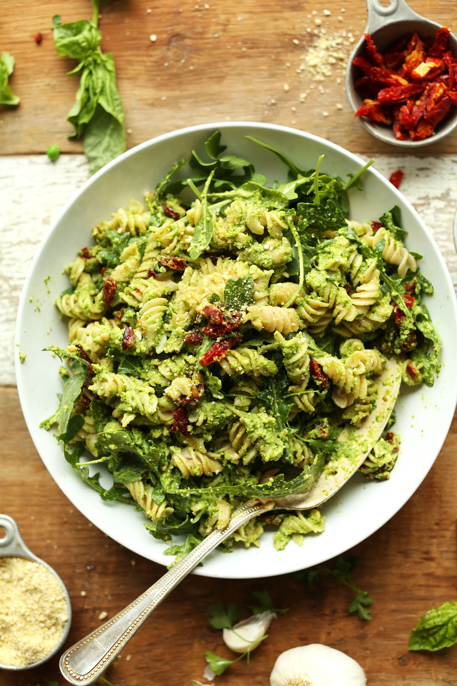 Big bowl filled with gluten-free vegan Pea Pesto Pasta with Sun-Dried Tomatoes and Arugula