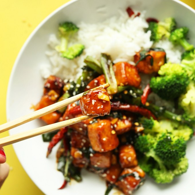 Using chopsticks to grab a bite of our General Tso's Tofu recipe for a delicious vegan dinner