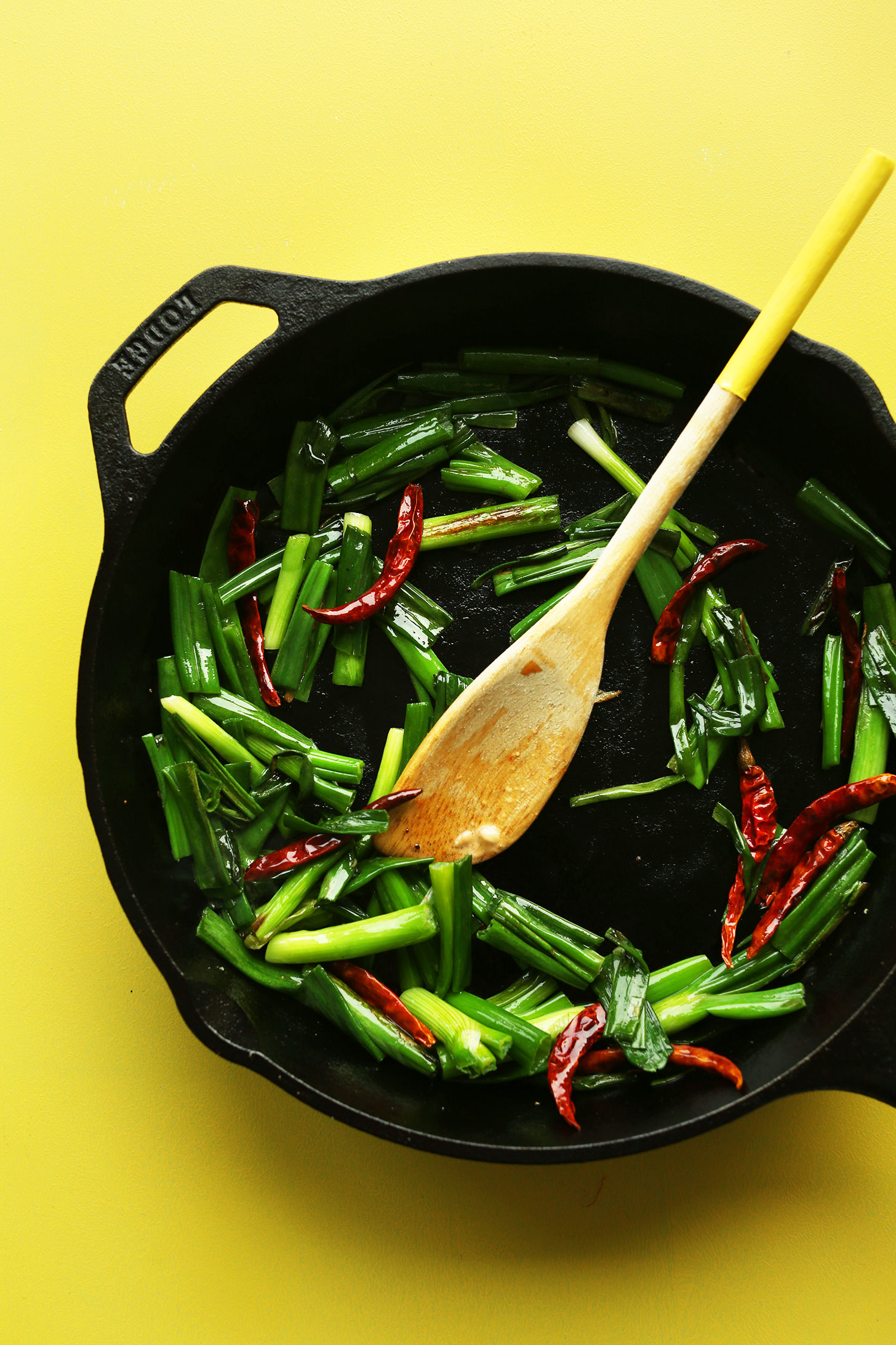 Sautéing green onions and red chilies in a cast-iron skillet