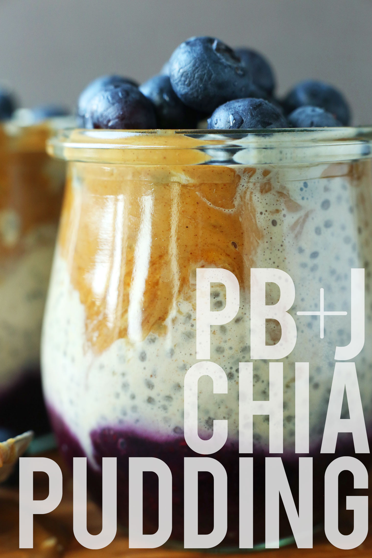 Close up shot of a jar of Peanut Butter and Jelly Chia Pudding topped with fresh blueberries