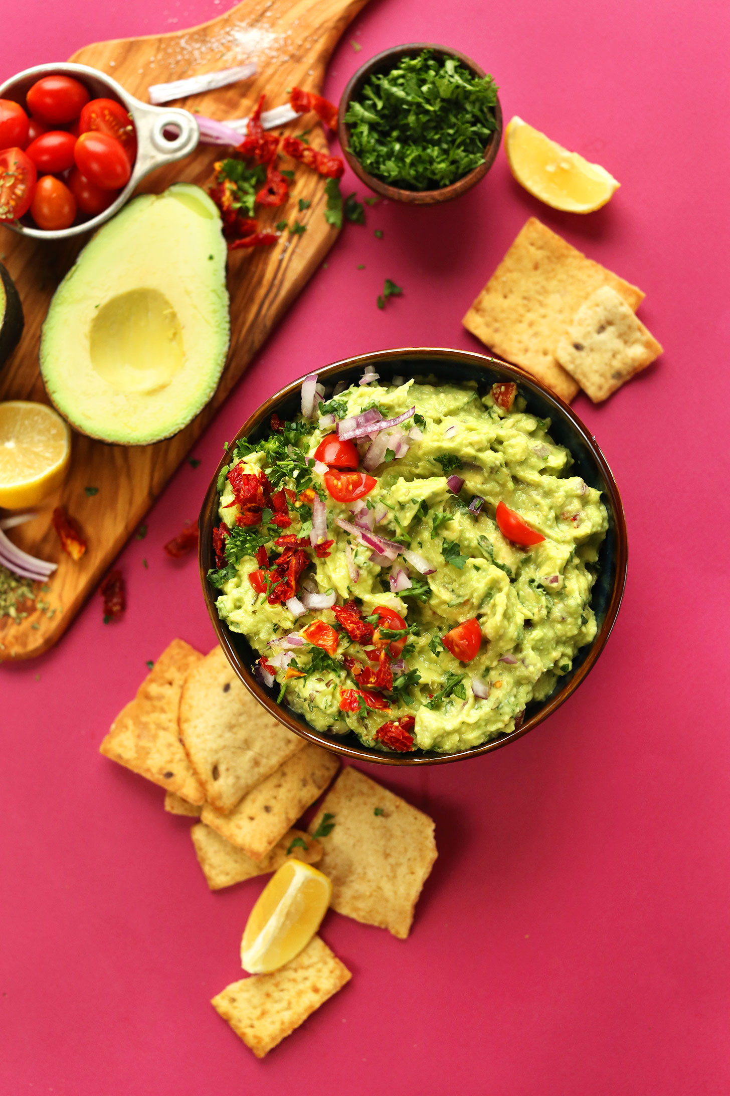 Bowl of vegan Greek-inspired Guacamole with crackers for dipping