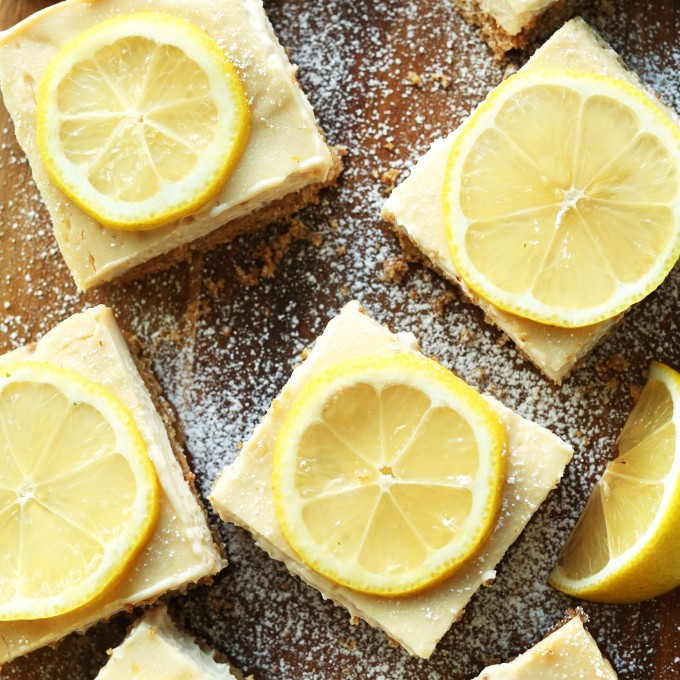 Squares of delicious homemade vegan gluten-free lemon bars on a wood board