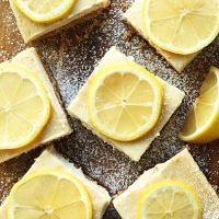 Batch of Creamy Vegan Lemon Bars topped with lemon slices and powdered sugar