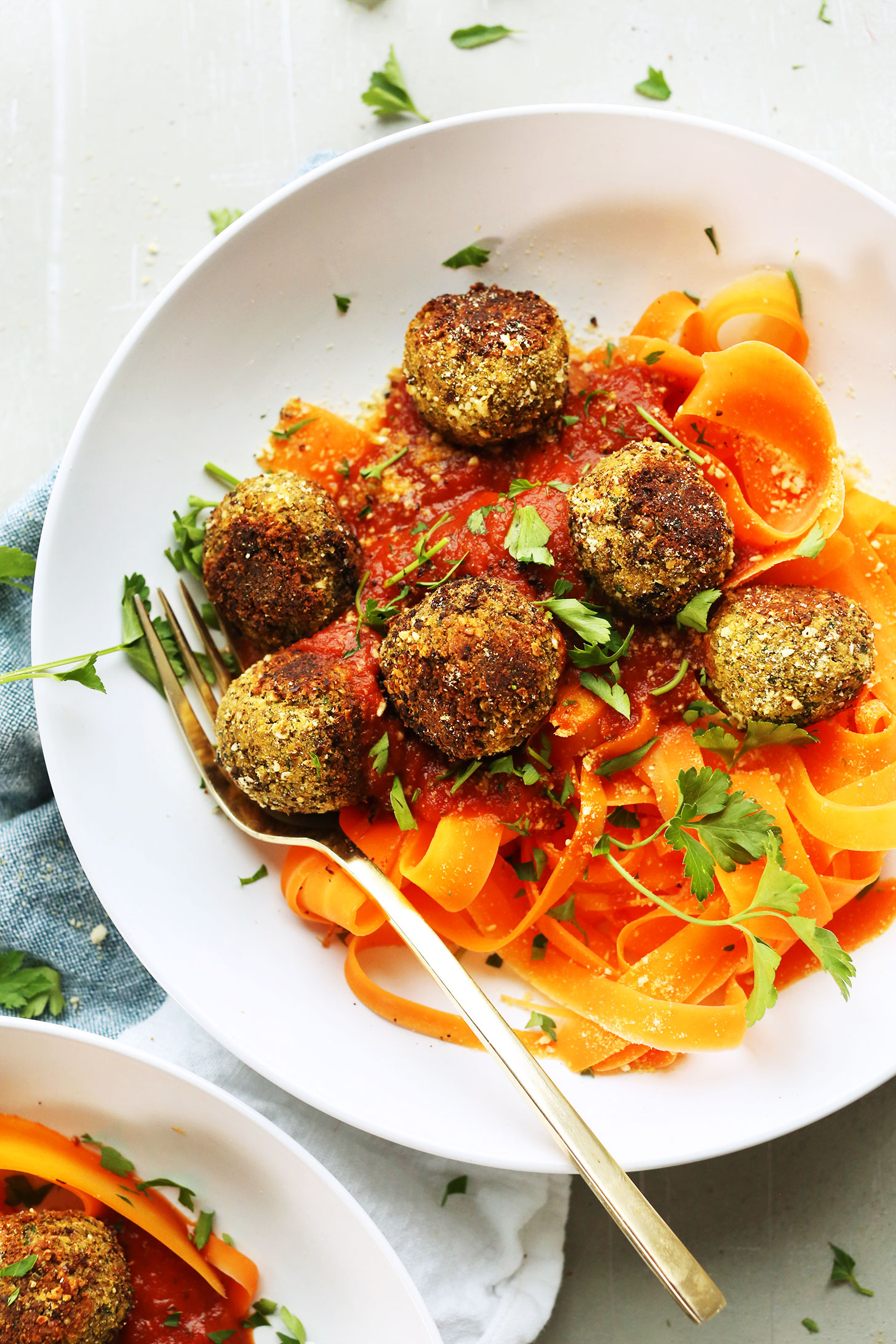 Bowl of carrot ribbons topped with our easy vegan lentil meatballs recipe