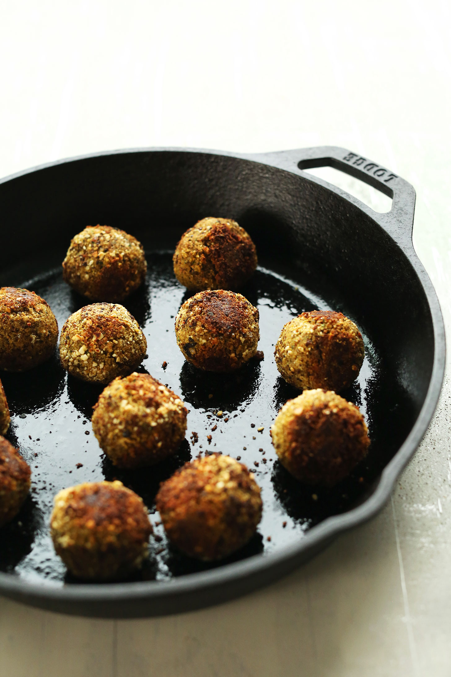 Browning vegan lentil meatballs in a cast-iron skillet for a delicious plant-based meal