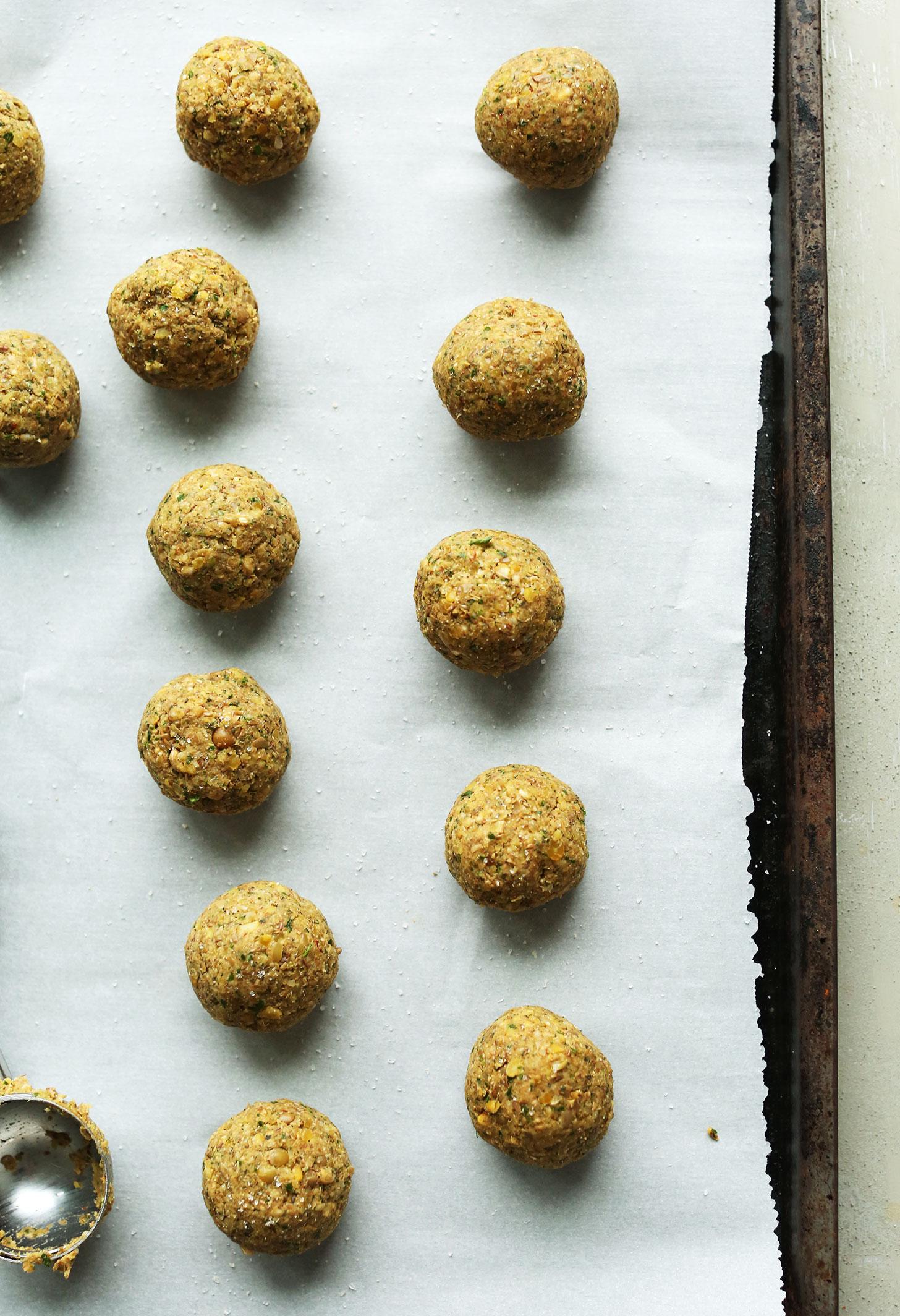 Parchment-lined baking sheet with freshly rolled vegan lentil meatballs