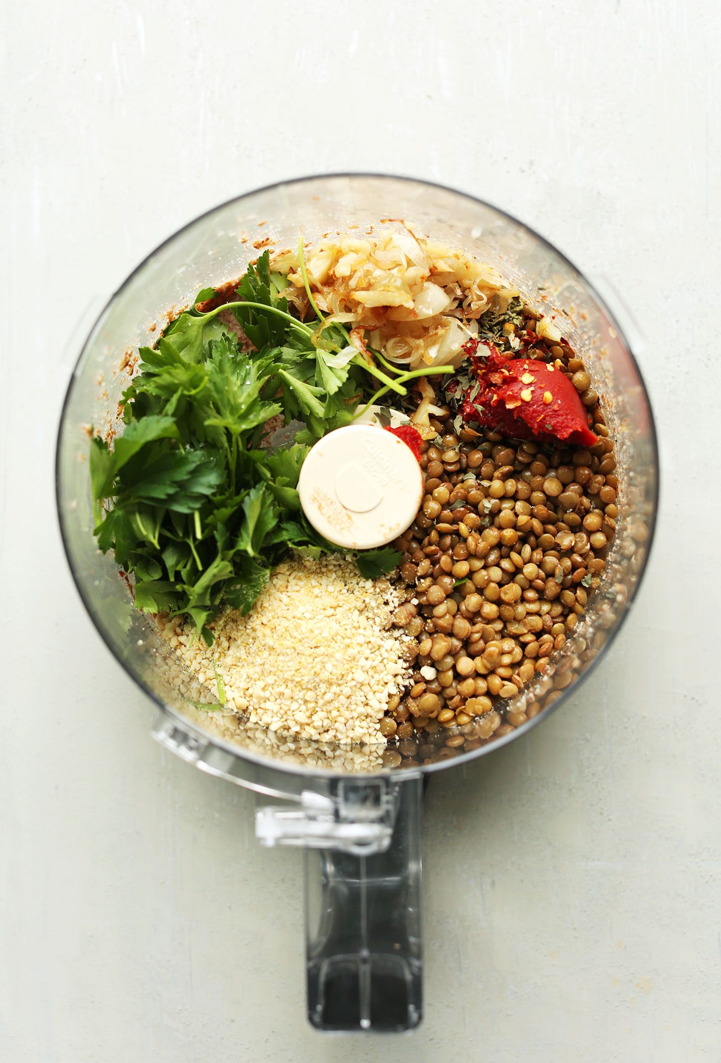 Food processor with ingredients for our protein-packed vegan lentil meatballs recipe