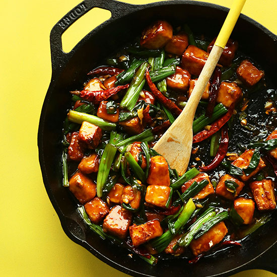 Wooden spoon resting on a skillet filled with our General Tso's Tofu Stir Fry recipe