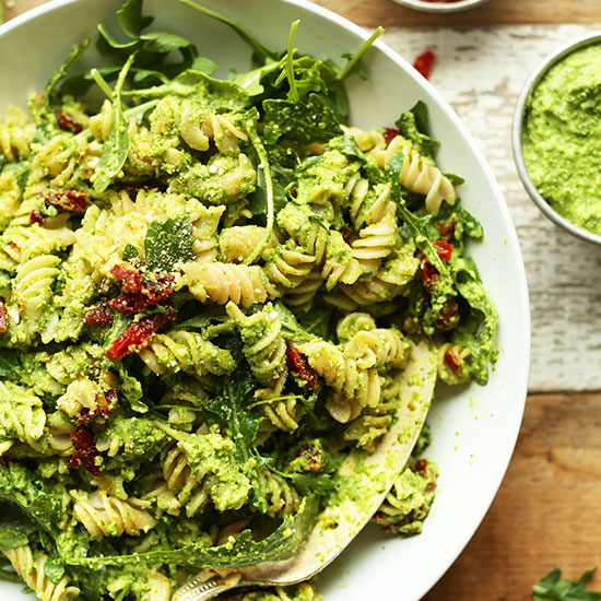 Big bowl of Gluten-Free Vegan Pea Pesto Pasta made with sun-dried tomatoes and arugula