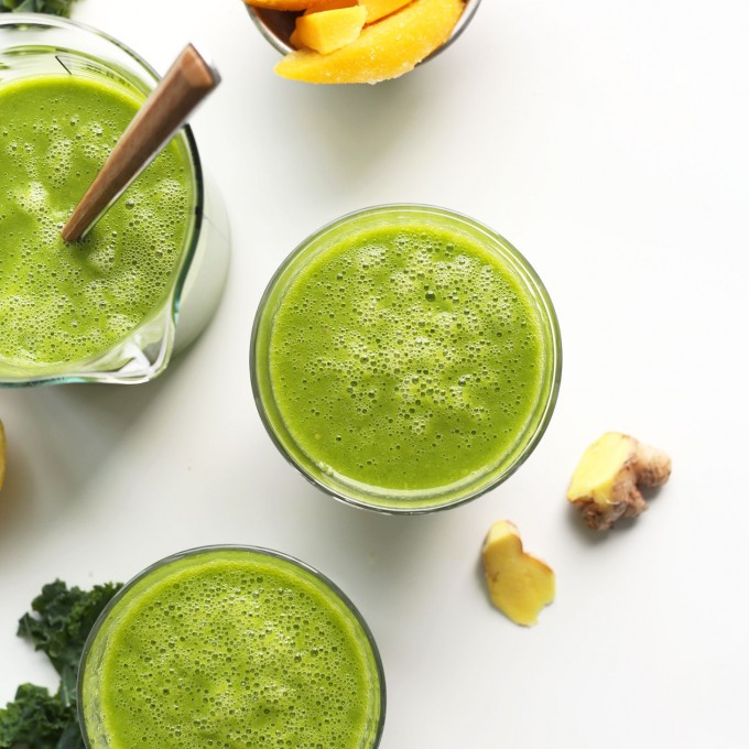 Glasses of our delicious vegan green smoothie made with ginger, lemon, peach, mango, and kale