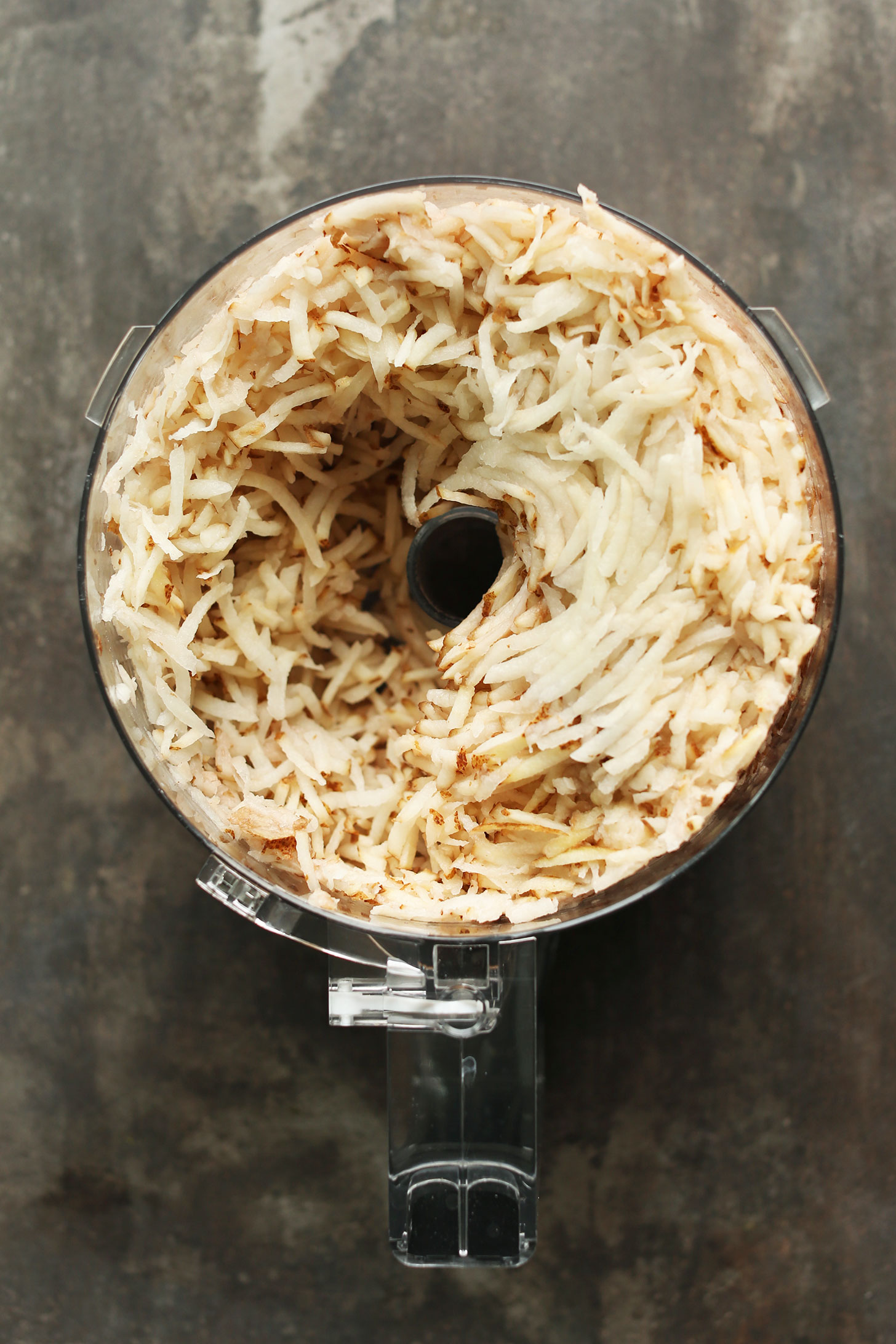 Food processor with grated potatoes for making into delicious crispy hashbrowns