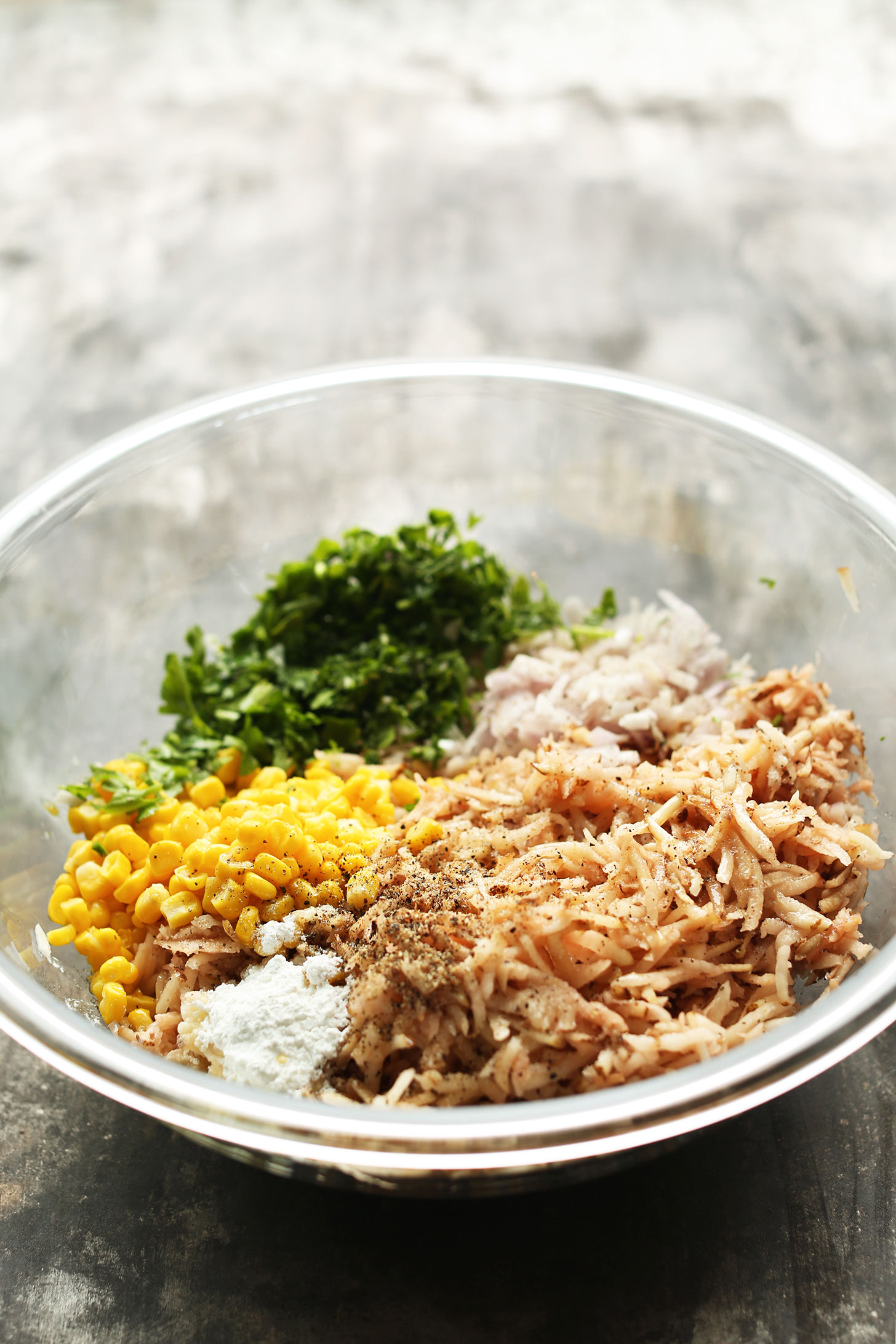 Mixing bowl with ingredients for making Crispy Hash Browns with corn, parsley, and shallot