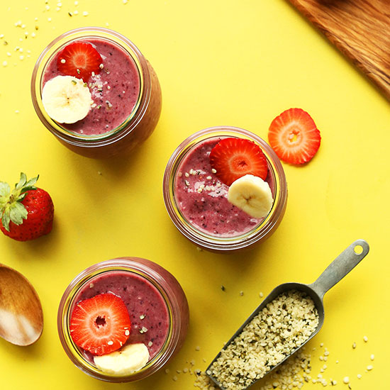 Three small jars of Banana Berry Hempseed Pudding topped with sliced fruit