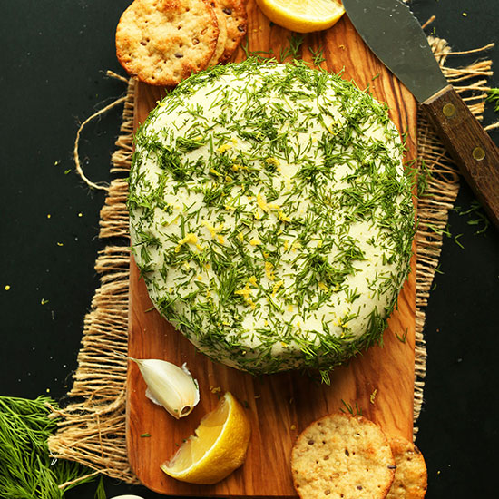 Dill Garlic Vegan Cheese Wheel on a wood cutting board with crackers