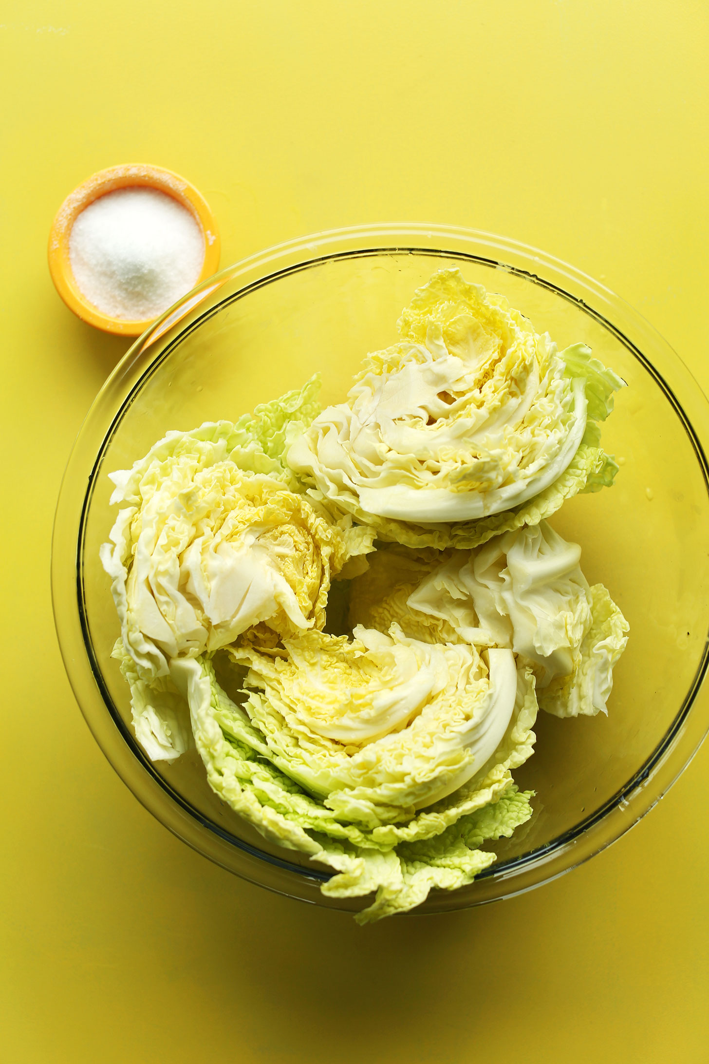 Bowls of cabbage and salt for making delicious our easy vegan kimchi recipe