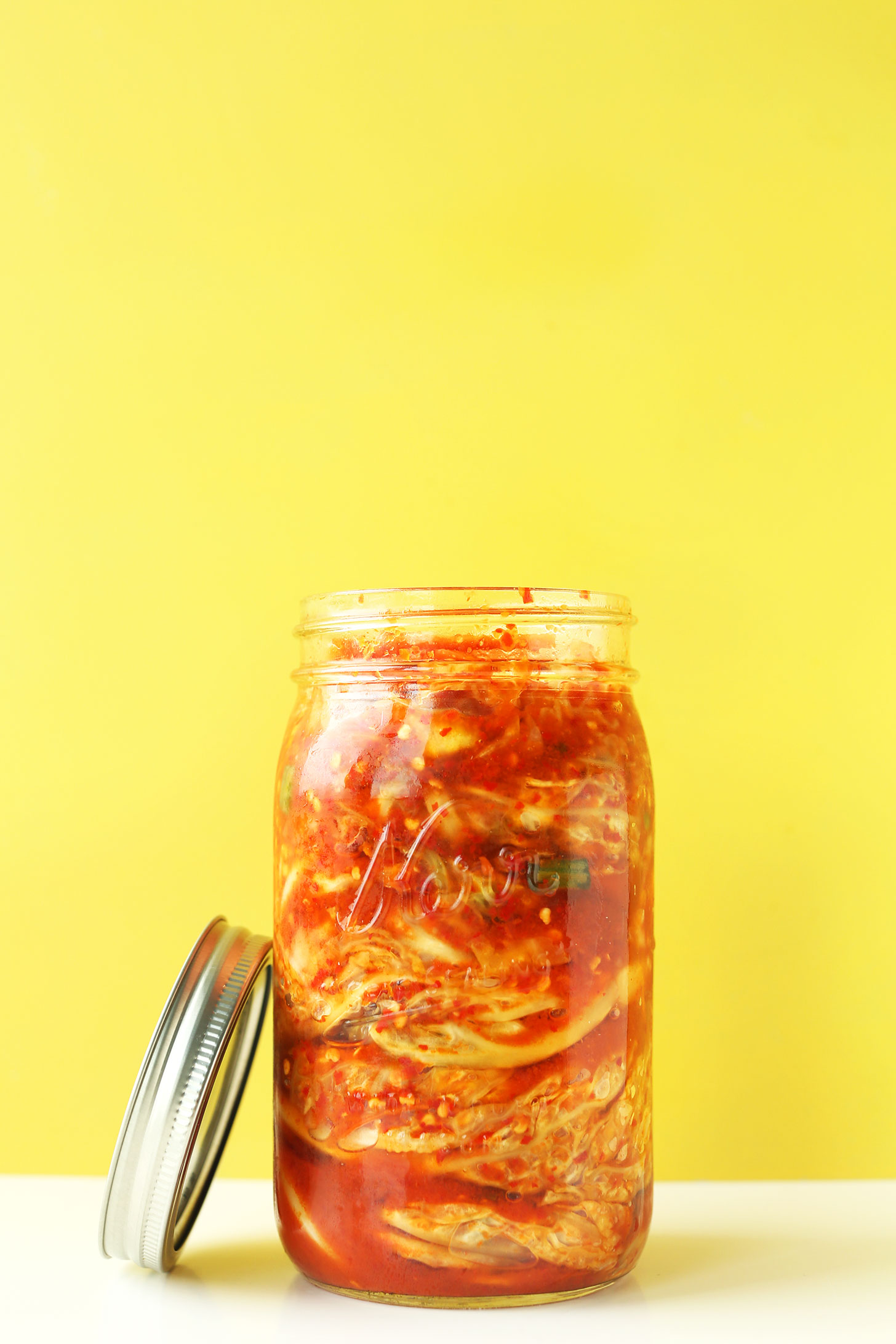 Jar of our easy kimchi recipe with the lid resting on the side