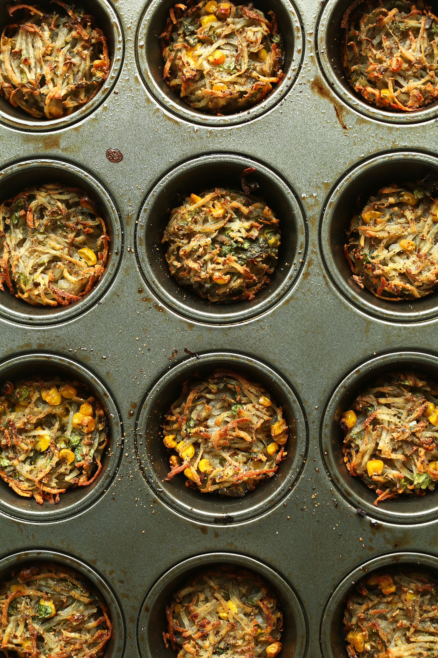 Muffin tin filled with hashbrown mixture for making Crispy Baked Hashbrowns