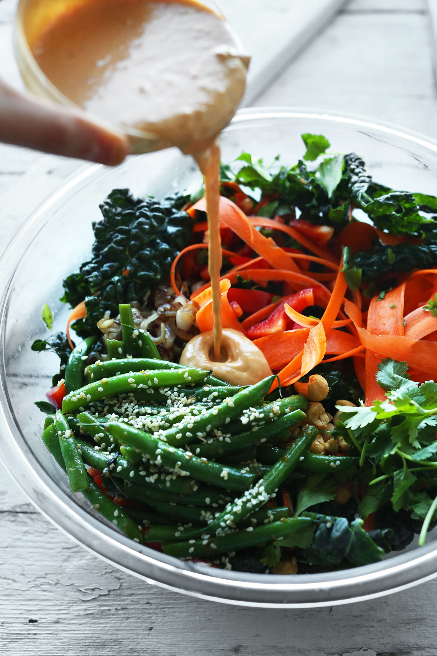 Pouring homemade gingery Cashew Dressing onto our Thai Kale Salad recipe