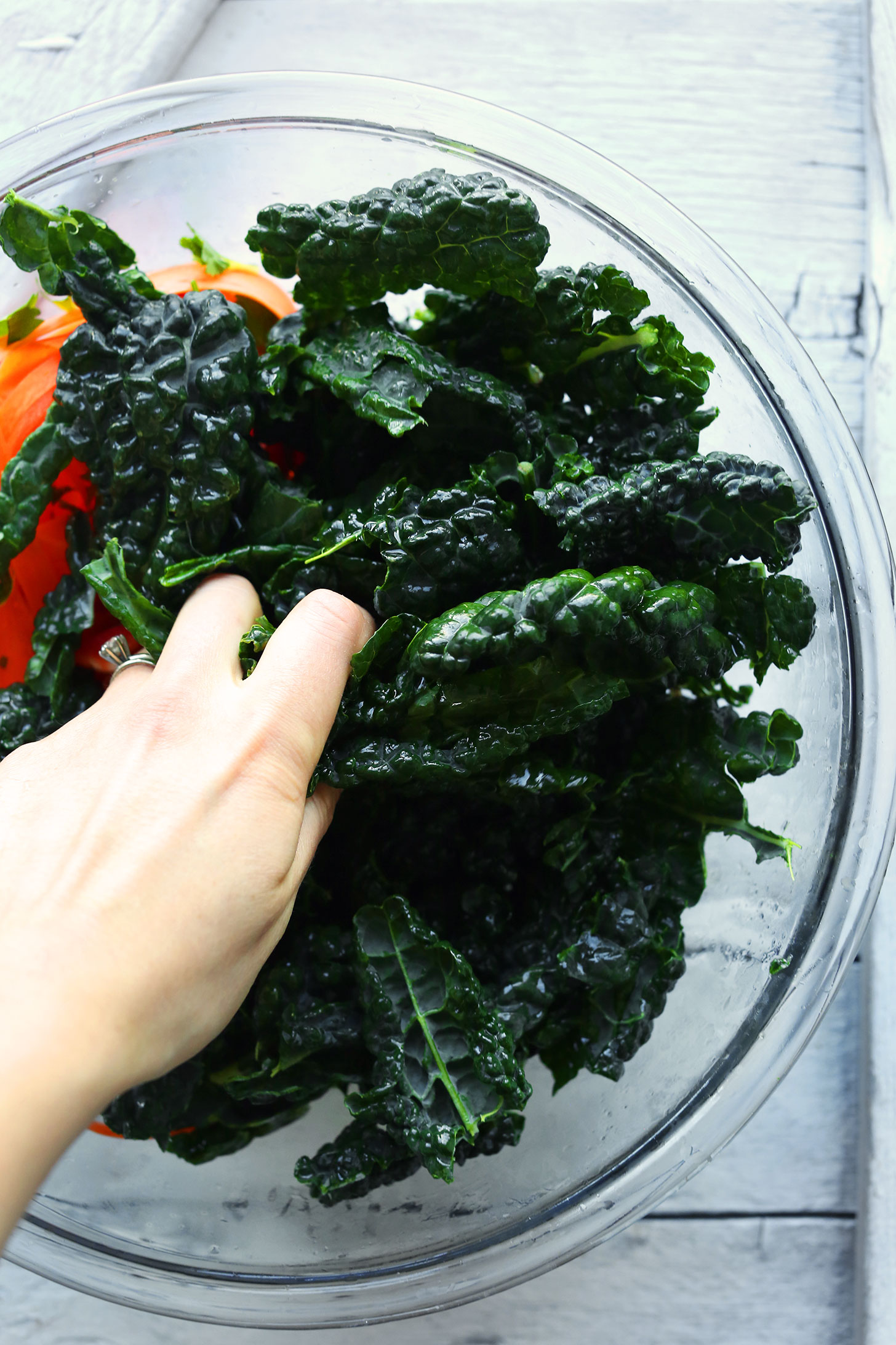 Adding kale leaves to a bowl for Gingery Thai Kale Salad made with tons of veggies