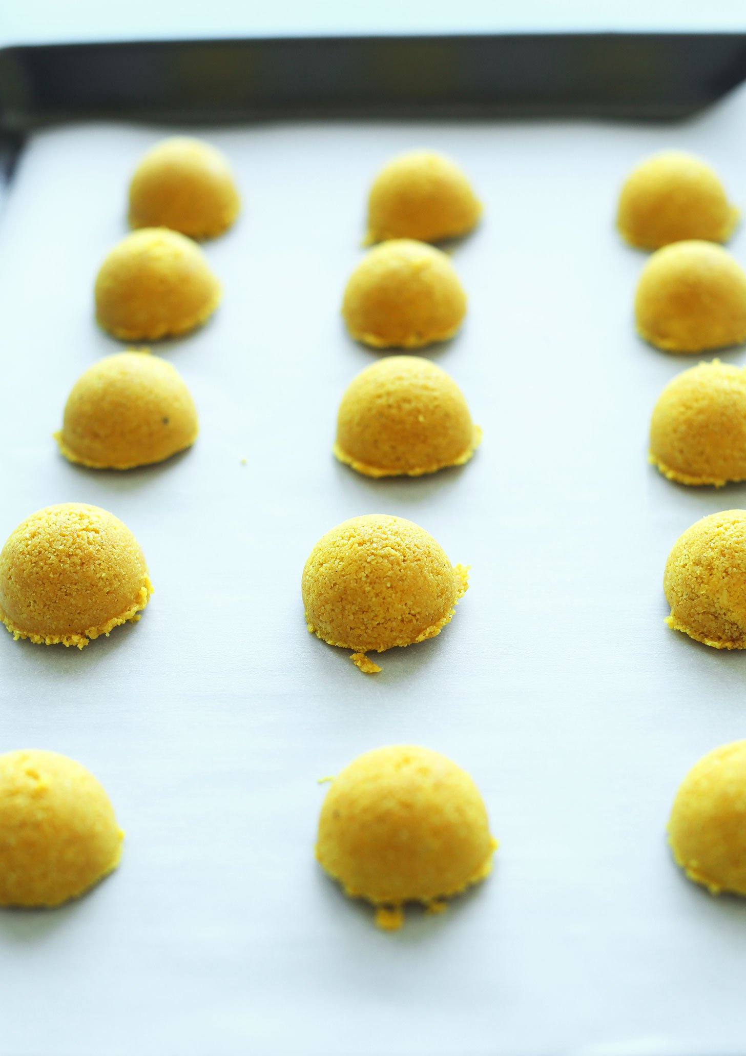 Parchment-lined baking sheet with perfect mounds of our Golden Milk Macaroons recipe