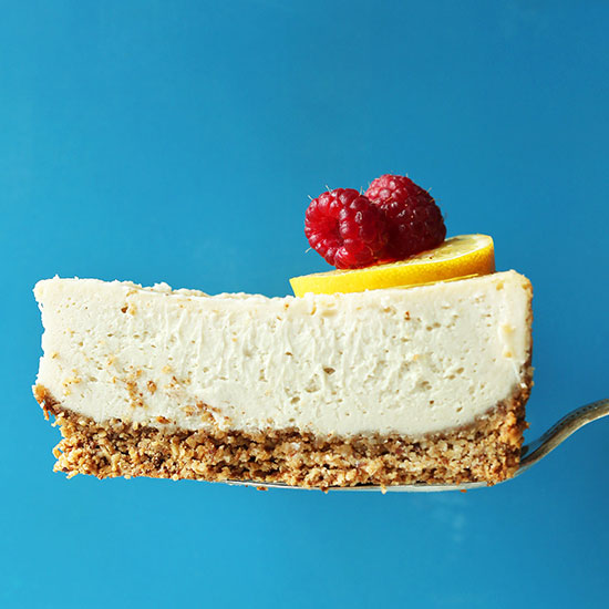 Holding up a slice of Easy Baked Vegan Cheesecake topped with lemon and raspberries