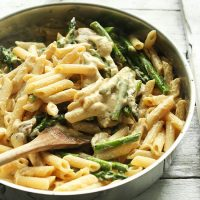 Wooden spoon in a skillet of Creamy Vegan Mushroom Asparagus Pasta