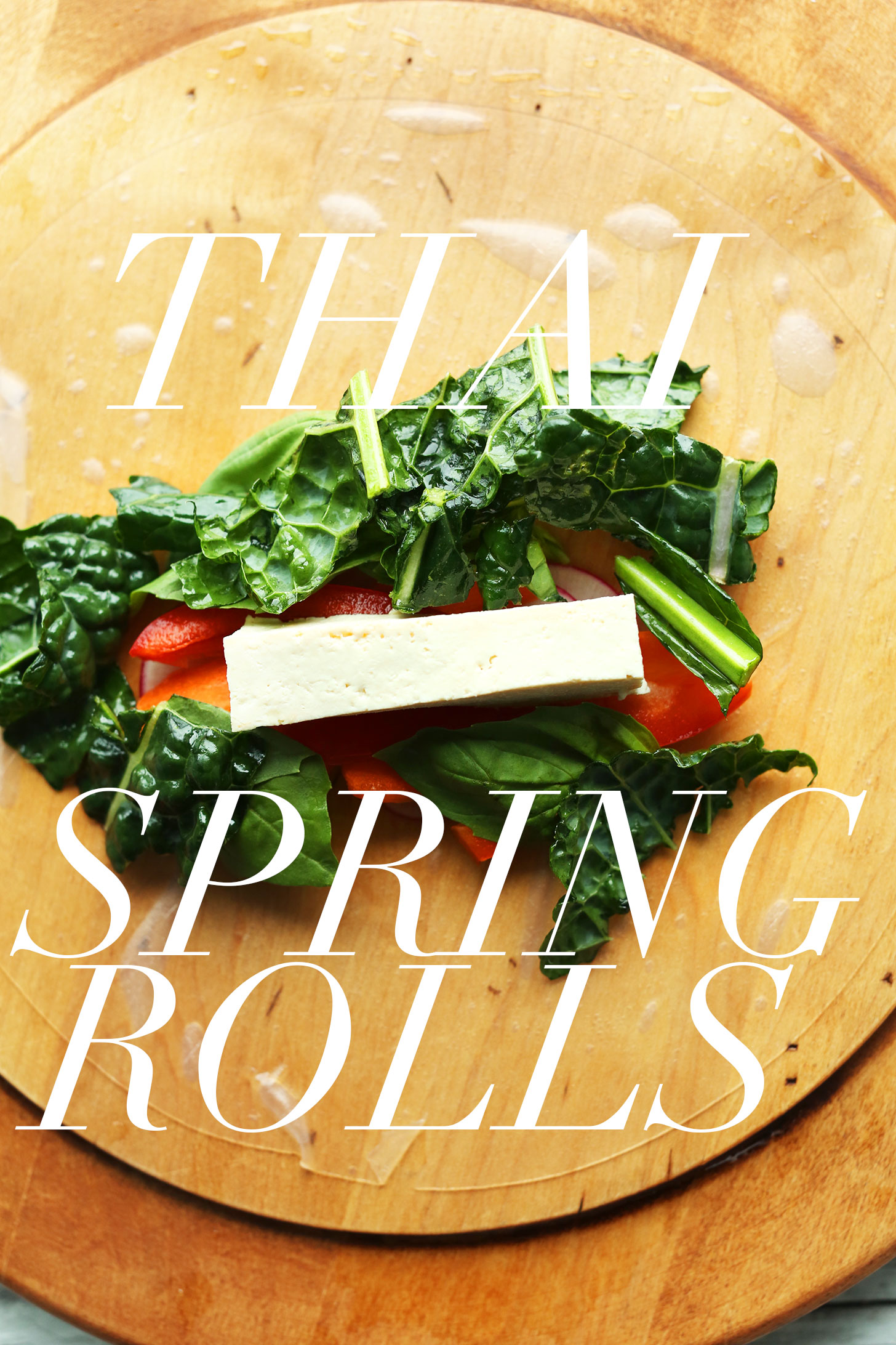 Wood cutting board with rice paper wrapper topped with ingredients for making Healthy Thai Spring Rolls
