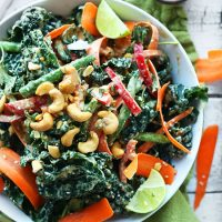 Big bowl of our amazing Gingery Thai Kale Salad topped with cashews and lime wedges