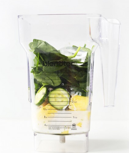 Blender filled with ingredients for our refreshing Cucumber Smoothie with Pineapple, Greens, Lime and Coconut