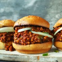 Wood board with three buns filled with sliced onions and our Vegan Sloppy Joe recipe