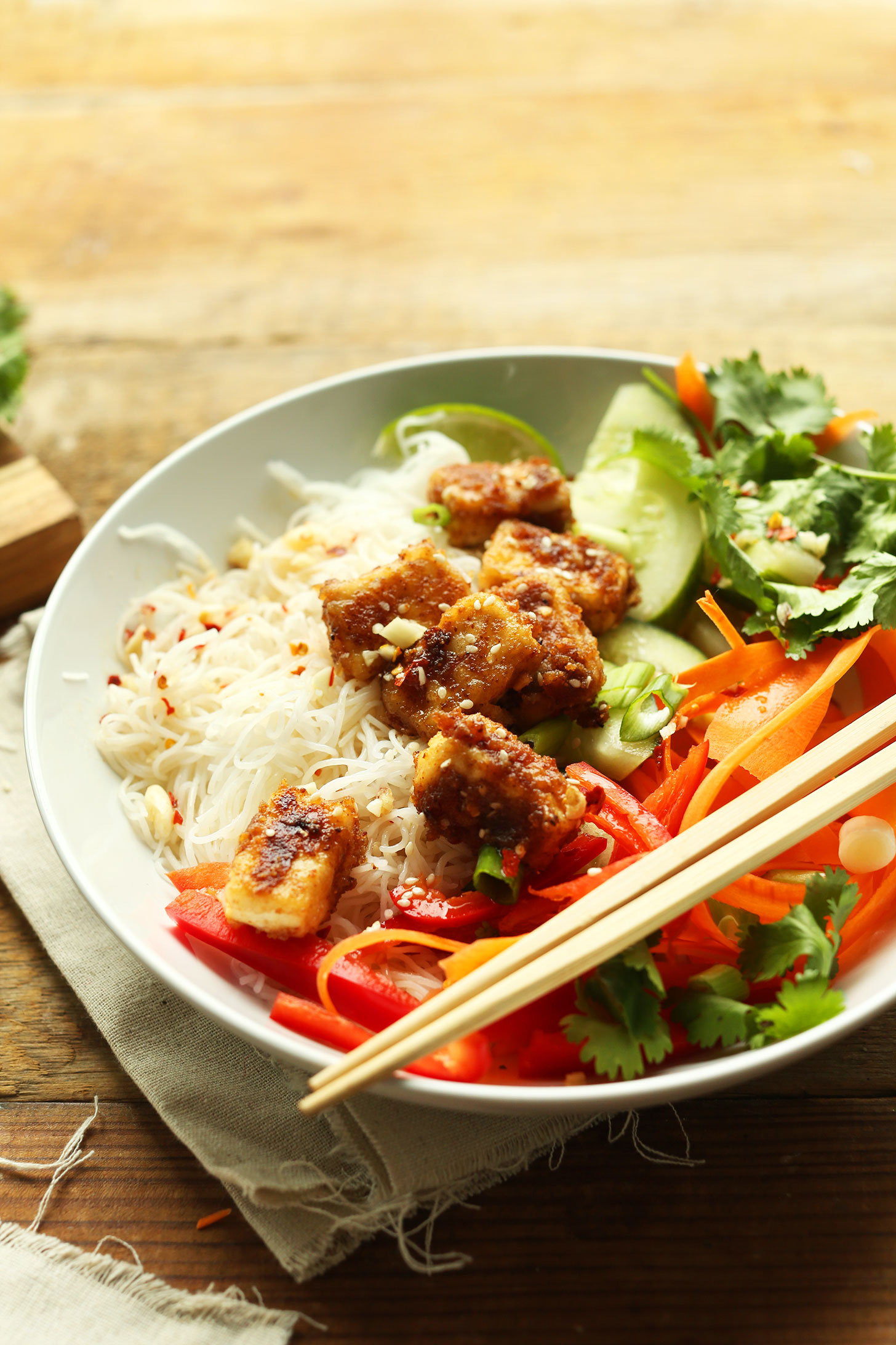 Chopsticks resting on a gluten-free vegan Thai Noodle Bowl with Crispy Almond Butter Tofu