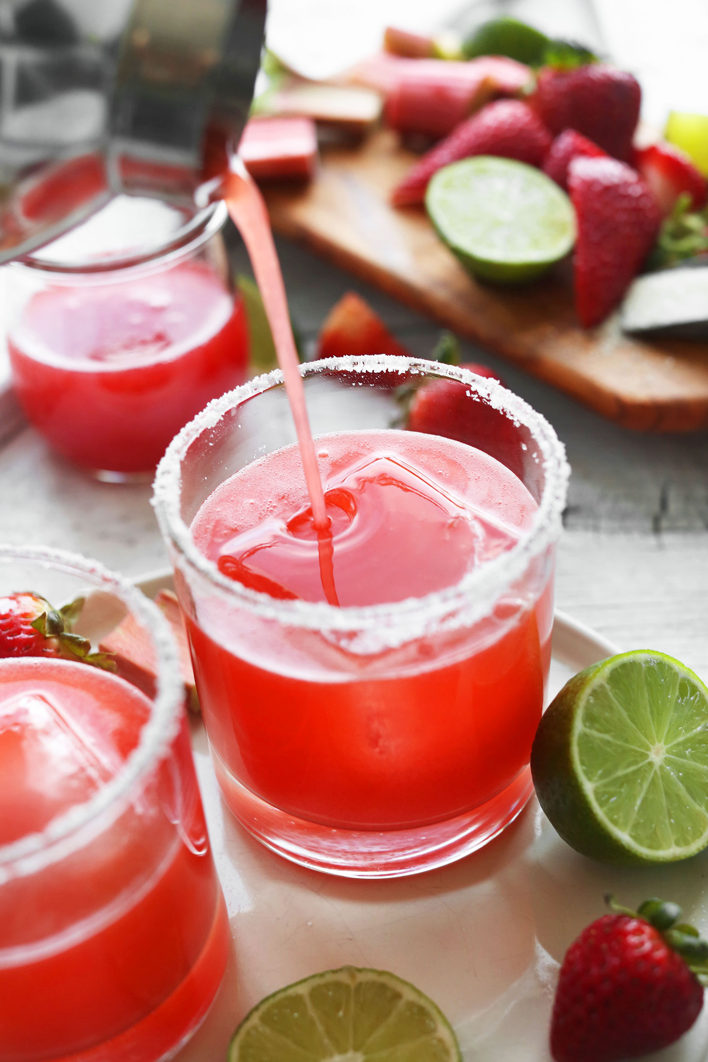 Pouring our gluten-free vegan Strawberry Rhubarb Margarita recipe into a glass