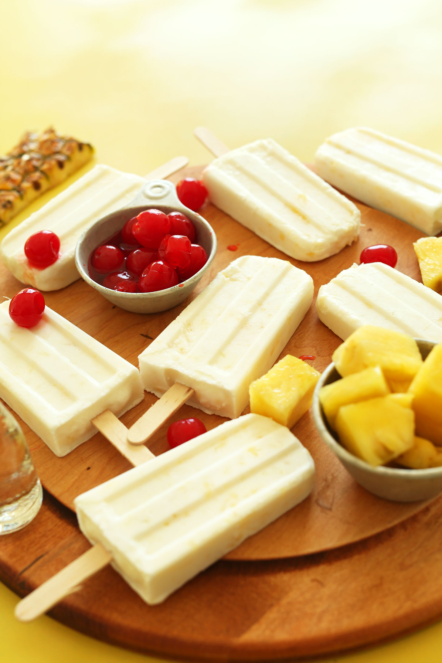 Homemade refreshing Pina Colada vegan Popsicles surrounded by fresh fruit