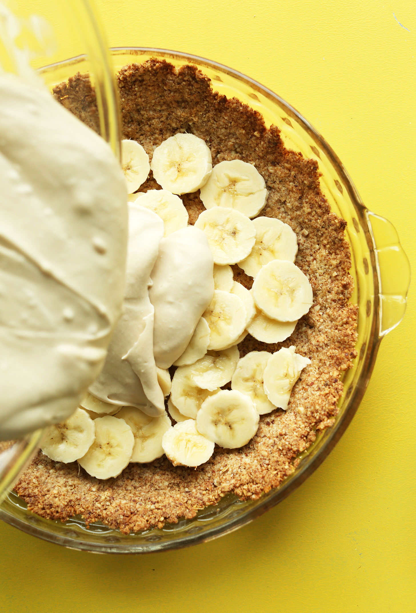 Pouring filling over the crust and banana layers for our gluten-free vegan Banana Cream Pie