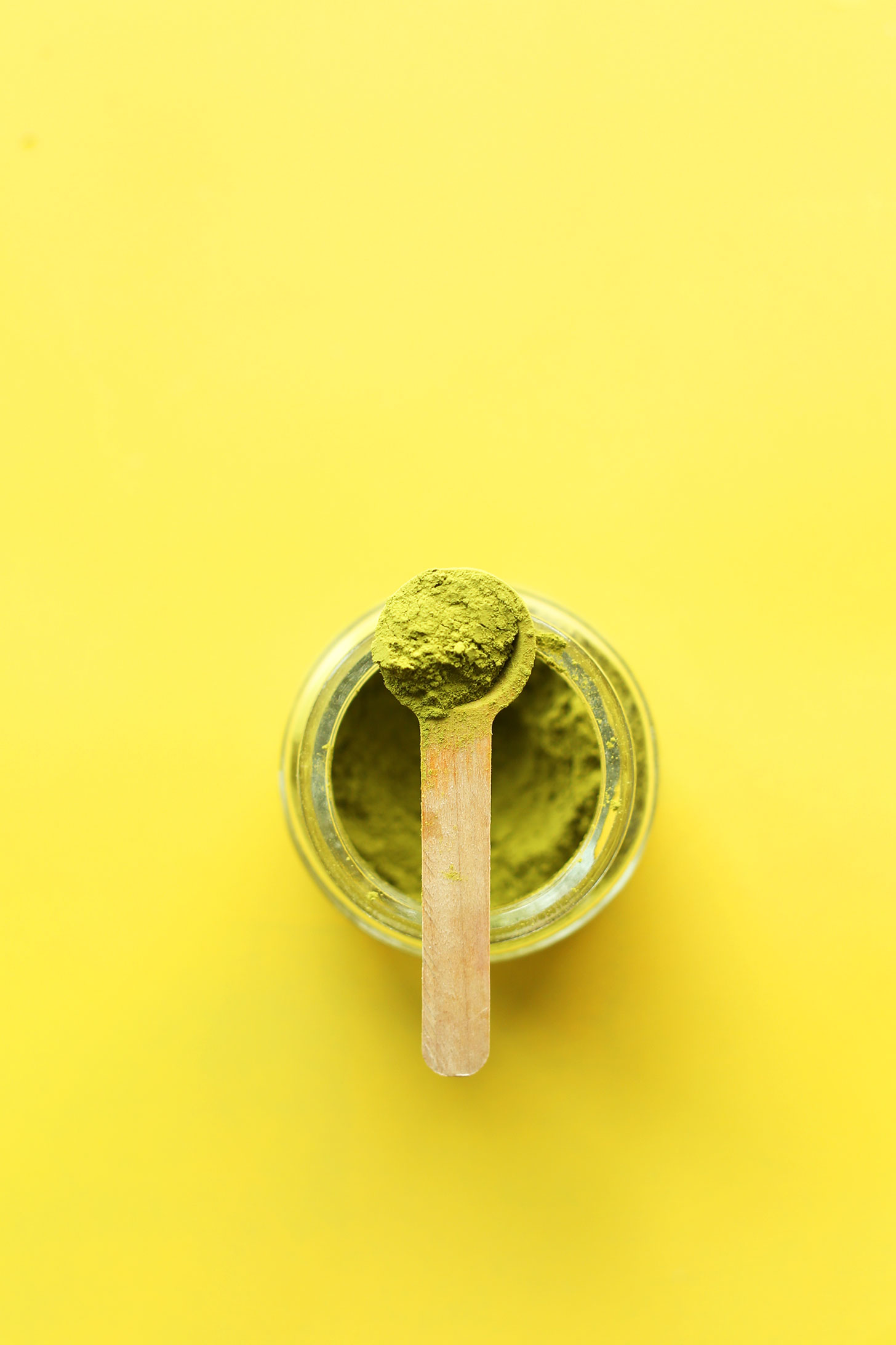 Small scoop of matcha resting on a jar