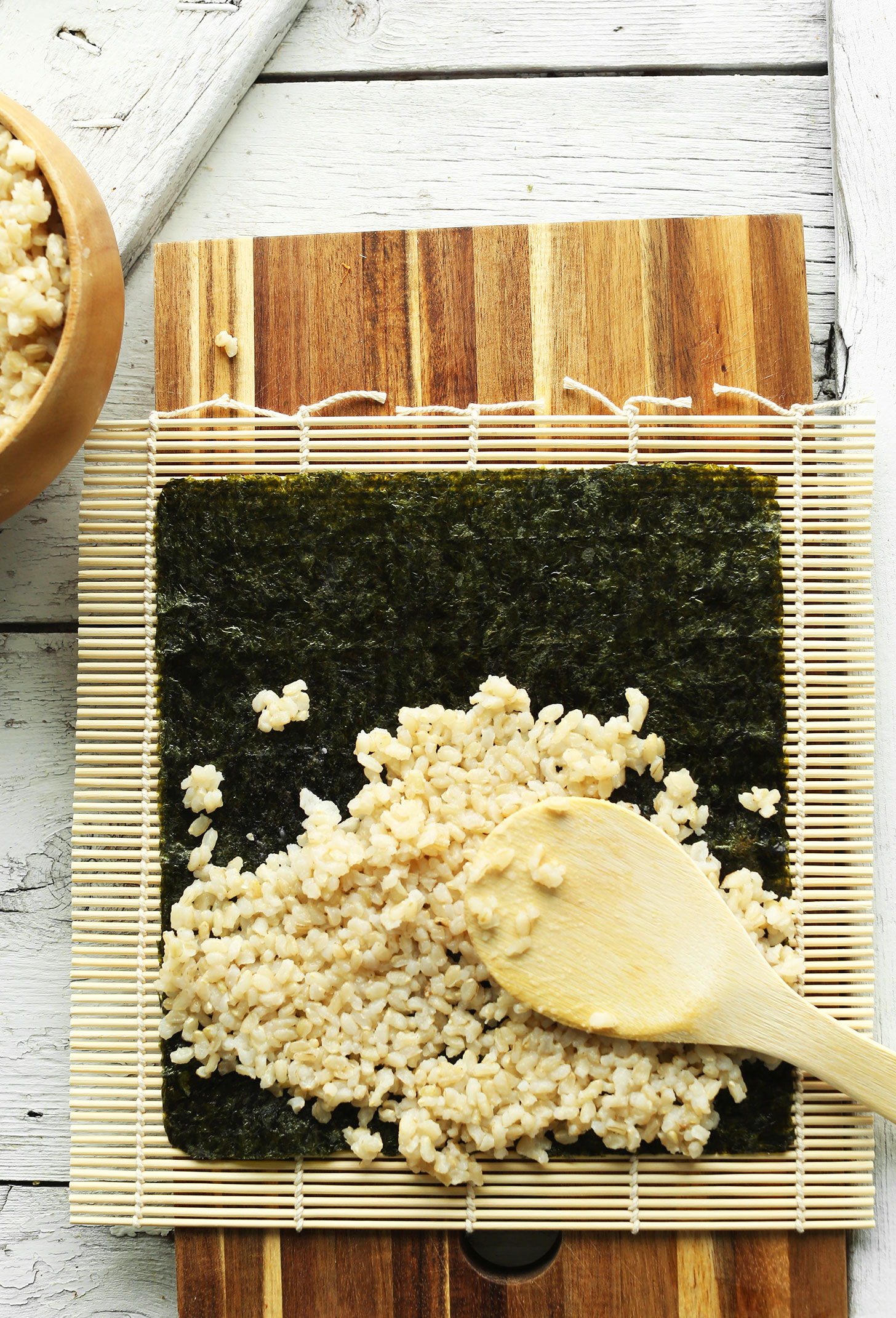 Spreading rice onto a sheet of nori for making homemade vegan sushi