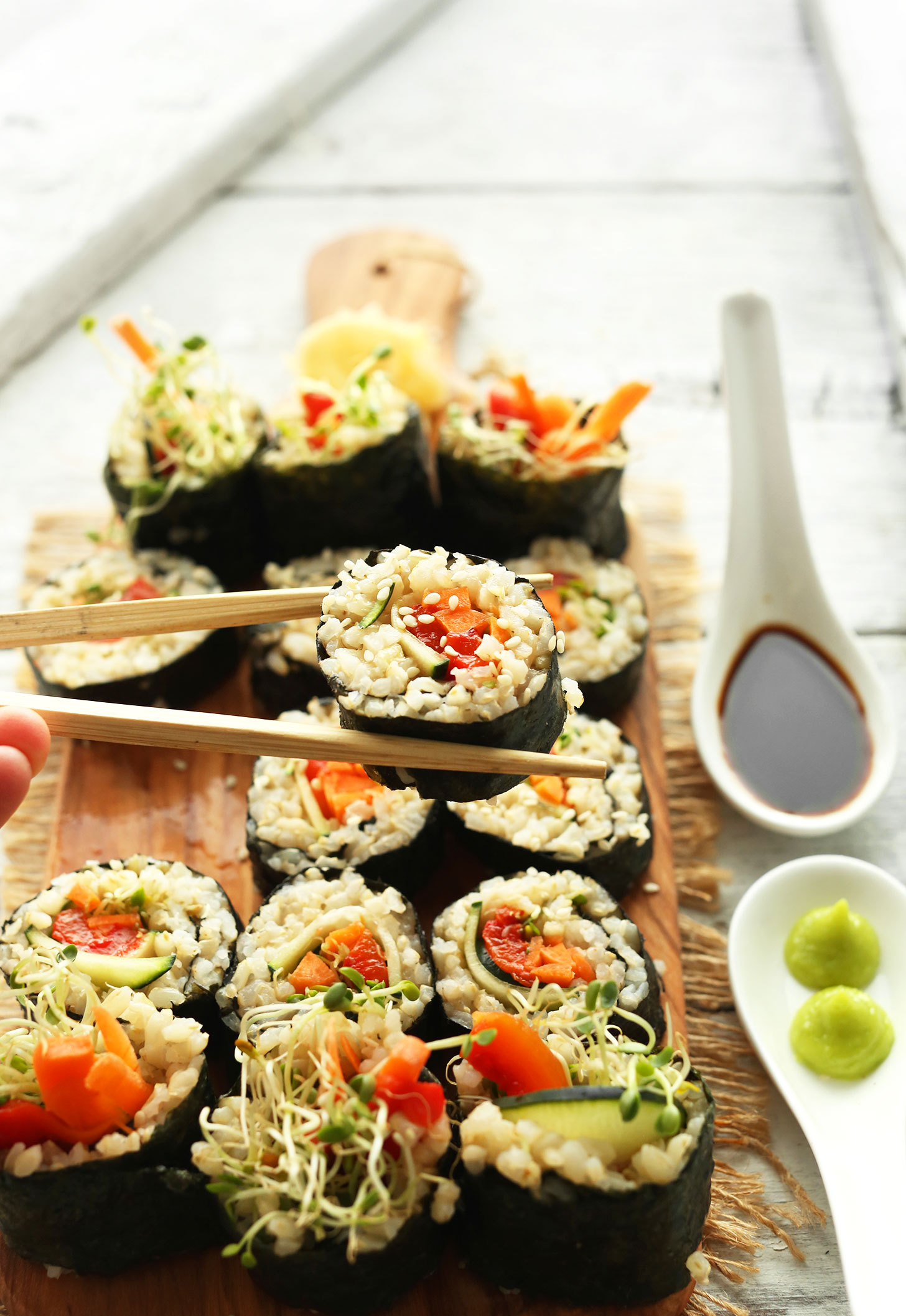 Using chopsticks to pick up a roll of our Vegan Brown Rice Sushi