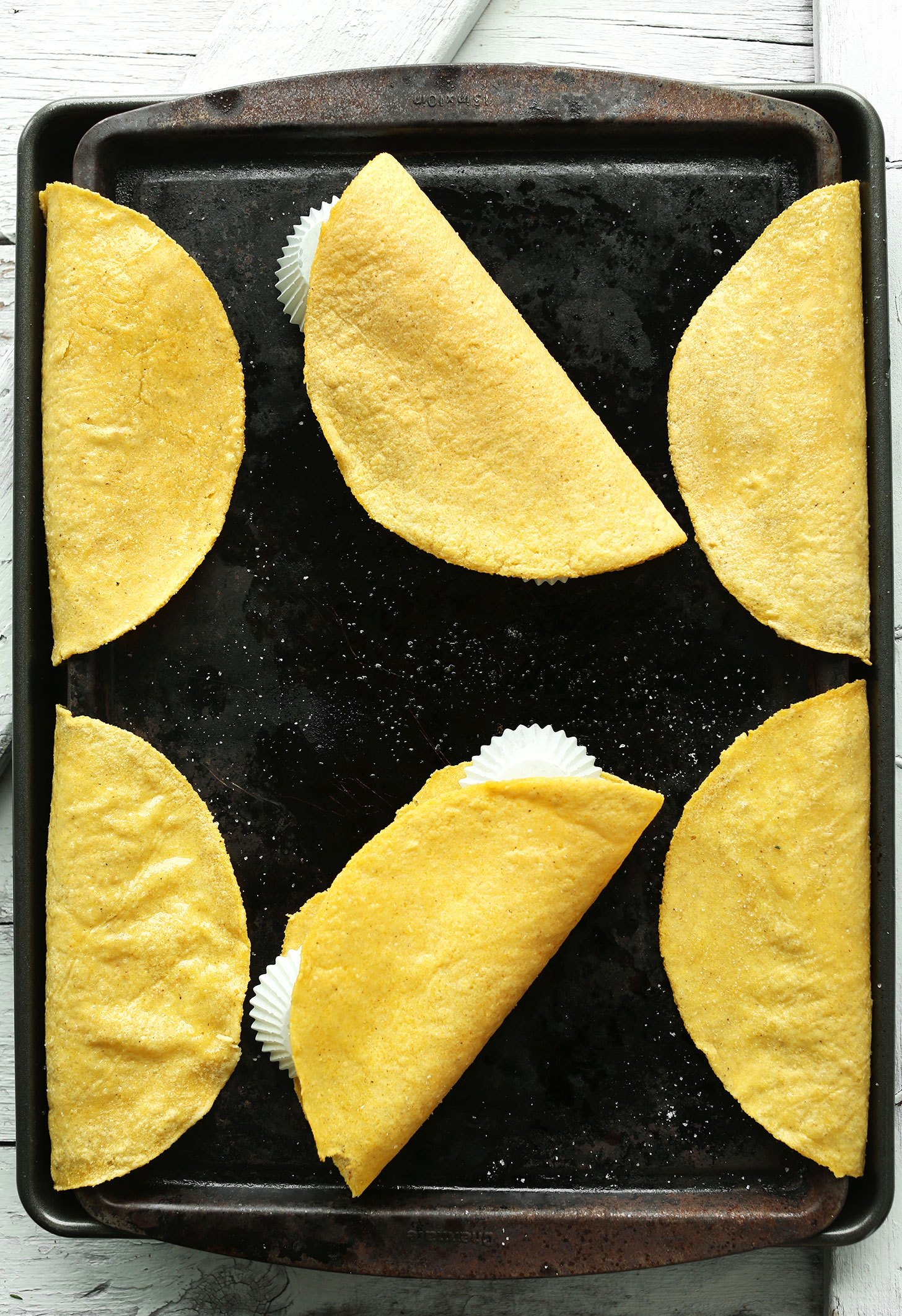 Baking sheet showing how to make homemade Crispy Baked Corn Taco Shells